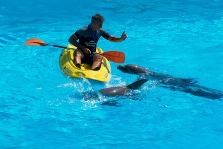 A man in a lifeboat floating next to the dolphins Stock Photo - 140760080