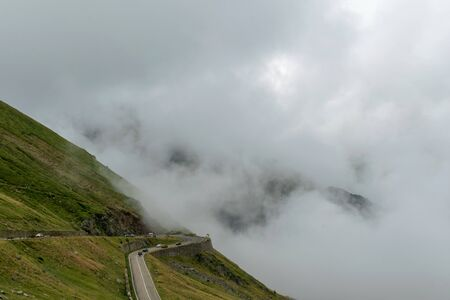 The road that crosses the Fagaras mountains seen from above among the fog, Transfagarasan, Romania