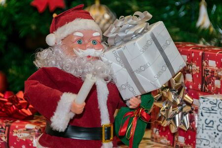 Santa Claus sitting close to the Christmas tree with a gift in his hand