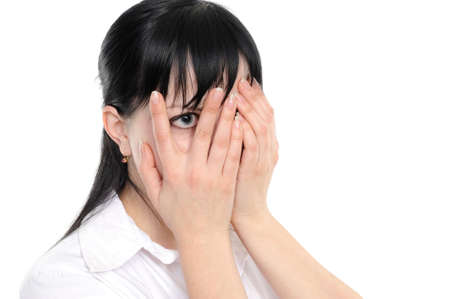 Young woman  is gazing through her fingers on a white background photo