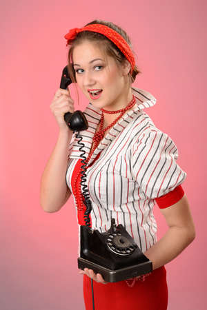 Beautiful  woman with holding a vintage phone photo