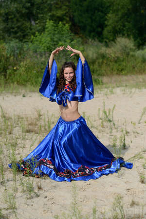Beautiful woman in long dress posing at the sand place