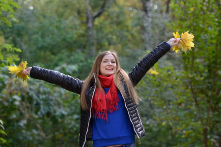 puzzlement: Beautiful  woman standing up and raises her hands in the autumn fores Stock Photo