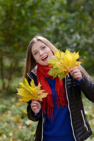 Beautiful  woman with Maple leaves standing in a park in autumn