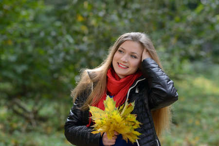 Young woman with autumn leaves in hand and garden background