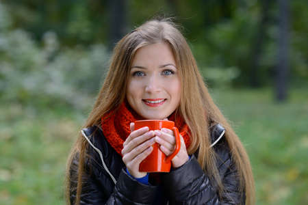 Outdoor autumn portrait of beautiful girl with cup of tea Stock Photo