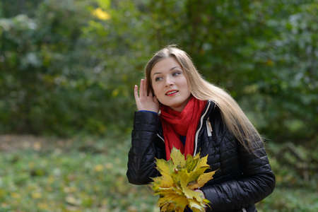 Young woman with autumn leaves in hand listening gossip Stock Photo