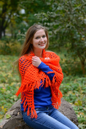 To coldly girl. The young woman is warmed by a scarf. Red lipstick. Stock Photo