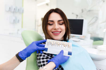 Dentist and his patient choose a tone of veneers. Dentistry doctor shows a palette with shades for teeth Stock Photo
