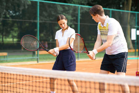 Young guy teaches a woman to play tennis. Couple with rackets in their hands on the tennis court