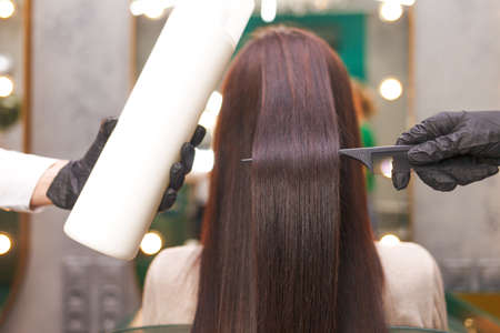 Straight and shiny hair after lamination. Hairdresser demonstrates the result of keratin hair straightening