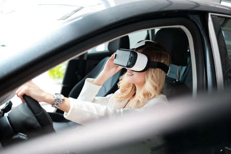 Pretty woman sitting in a car in 3D glasses of virtual reality