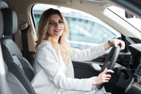 Young woman driving a car. Elegant business lady driving an expensive car