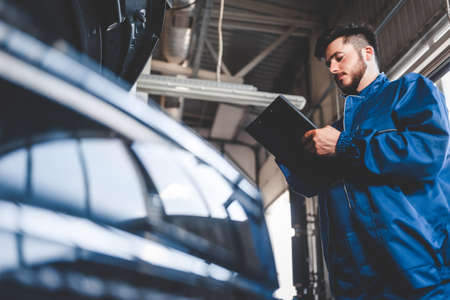 Car mechanic writes repair plan on clipboard. Auto service worker male