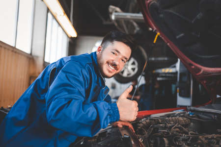 Auto mechanic showing thumbs up. Positive car mechanic concert Фото со стока
