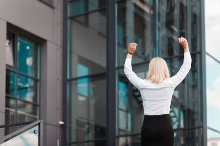 Woman happy about business success. Elegant female office worker celebrates success on the roof of a business center building Stock Photo
