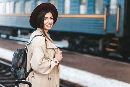 Portrait of young beautiful woman traveler who is waiting for a train on the platform of the railway station