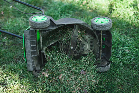 Lawn mower overflowing with grass lies on its side
