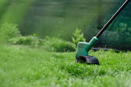 Mowing grass with electric trimmer