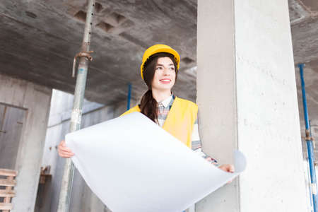 Girl engineer at construction site with drawings in hand Stockfoto