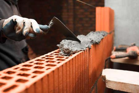 Bricklayer puts bricks to make a wall