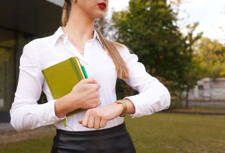 Business lady looks at her watch. Young girl hurries to a meeting