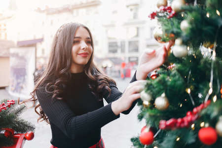 Pretty woman hangs a ball on the Christmas tree on the city street Imagens