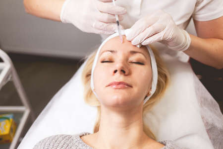 Ð¡osmetologist doctor injects botox into the patient's forehead
