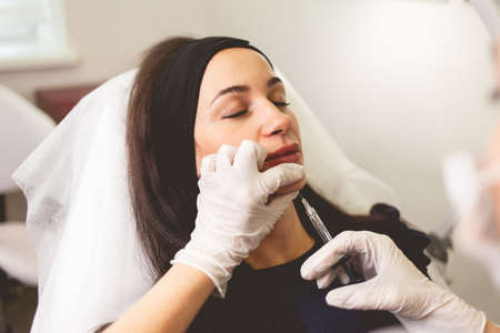Woman fights facial wrinkles. Doctor cosmetologist gives a chin injection for patient Foto de archivo
