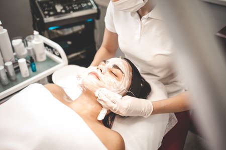 Cosmetologist washes off the mask from the patient's face. Removing a moisturizing mask from the face