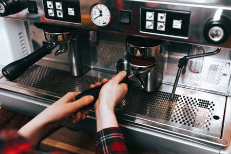 Barista makes aromatic coffee. Process of making latte coffee on a coffee machine in a cafe