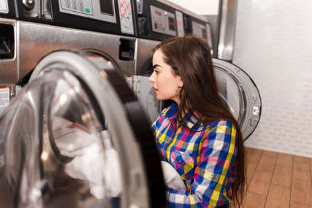 Girl loads laundry into a washing machine. woman in laundrette