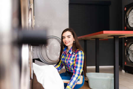 Young girl takes out washed clothes from a washing machine Stockfoto