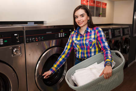 Girl with a basket of laundry opens the door of the washing machine in the public laundry