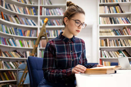 Schoolgirl in a plaid shirt leafing through a book while sitting in a library room. Young woman came to the library to prepare for the college exam. Girl in glasses develops reading books