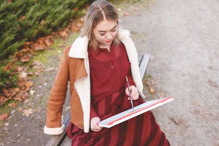 Young girl draws a picture on a park bench. Blonde artist engaged in her favorite hobby of drawing