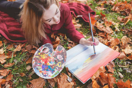 Young woman artist is relaxing in the park for her favorite hobby. Girl draws a picture, holding a palette in hand Stock Photo