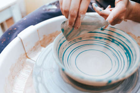 Professional potter works on painting plates in the workshop. Woman paints a ceramic plate with a brush and blue paint