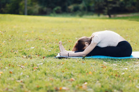 flexible sporty woman doing stretching yoga in park