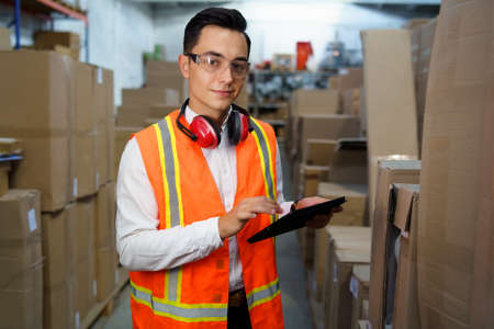 Portrait of a warehouse worker with a tablet in his hands