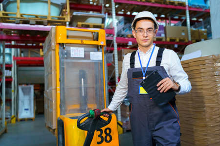 Man works in a warehouse with a forklift