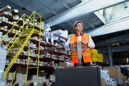 Warehouse worker operates a pallet loader