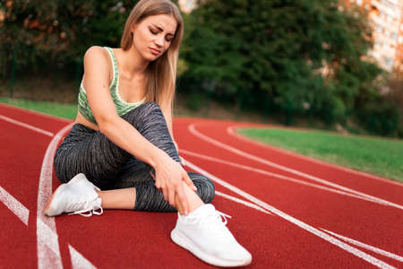Sports girl injured her ankle and holding her leg while sitting on the stadium track