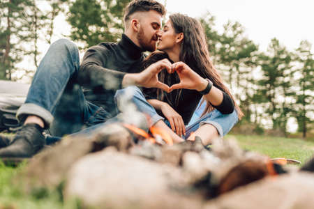 Romantic couple sitting near campfire kissing and showing heart shaped gesture