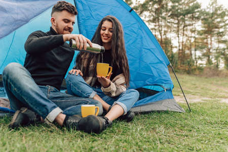 Happiness couple in nature with tent, drinking hot beverage. Man pours tea to his woman