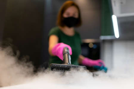 Woman employee cleaning company blows vapor out of steam generator. Steam cleaning process for kitchen furniture