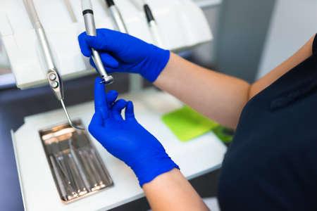 Dentist inserts burr on dental drill. Doctor preparing for dental treatment