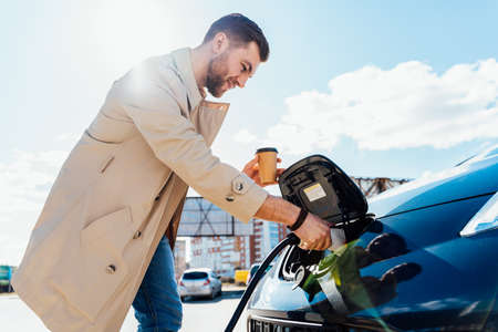 Stylish man with coffe cup in hand inserts plug into the electric car charging socket