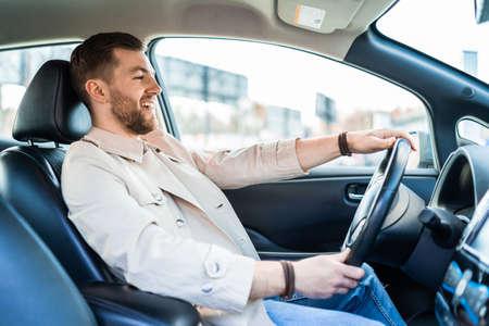 Smiling handsome man driving car