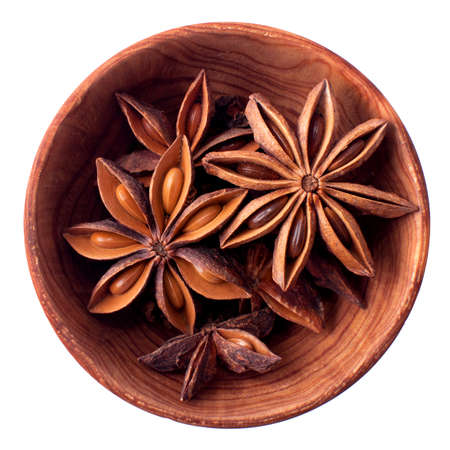Anise stars in a wooden bowl isolated on white